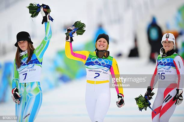 Tina Maze of Slovenia celebrates winning the silver medal Viktoria Rebensburg of Germany gold and Elisabeth Goergl of Austria bronze during the...