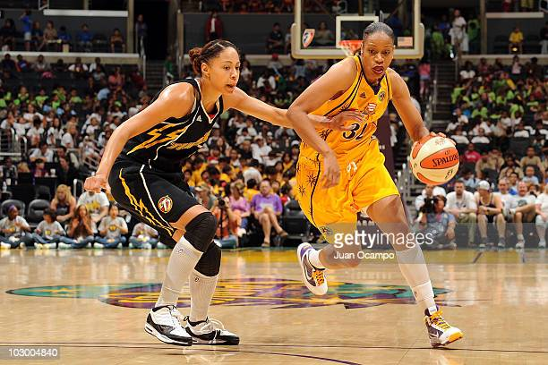 Tina Thompson of the Los Angeles Sparks drives against Jennifer Lacy of the Tulsa Shock on July 20 2010 at Staples Center in Los Angeles California...