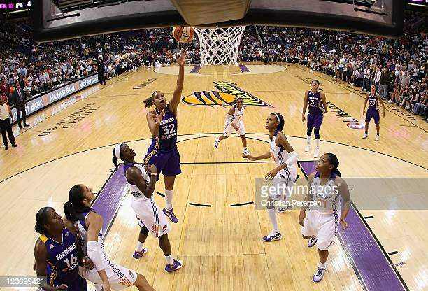 Tina Thompson of the Los Angeles Sparks puts up a shot over Marie FerdinandHarris of the Phoenix Mercury during the WNBA game at US Airways Center on...