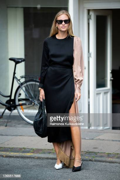 Tine Andrea outside Malaikaraiss wearing long black and beige dress longer on one side with one white and one black shoes during Copenhagen fashion...