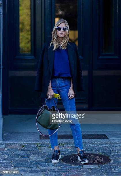 Tine Andrea weaing a green Fendi bag blazer and blue sweater outside YDE during the first day of the Copenhagen Fashion Week Spring/Summer 2017 on...