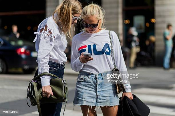 Tine Andrea wearing a Fendi bag and white top having a look on the phone of Nathalie Helgerud wearing a white Fila longshirt denim mini skirt and...
