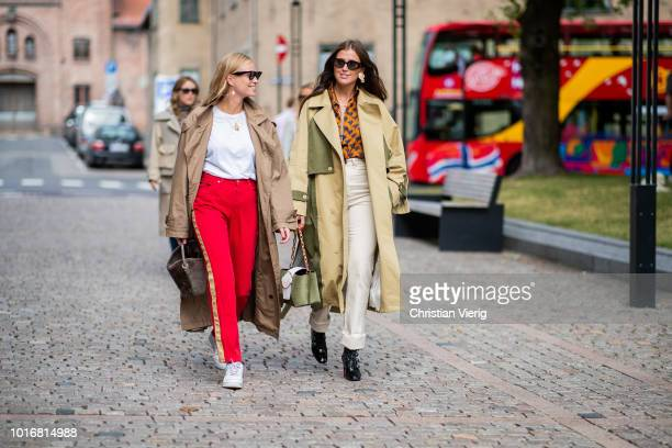 Tine Andrea wearing red pants and trench coat Darja Barannik wearing beige trench coat with slits creme white rolled pants ankle boots seen outside...