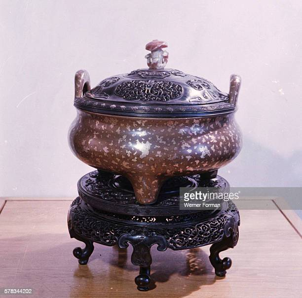 Ting cauldron with lid The surface of the bronze is decorated with spots of gold The lid is surmounted by a piece of rose carved quartz in the form...