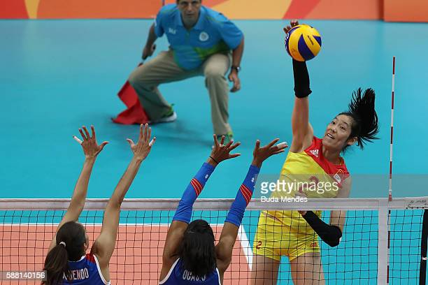 Ting Zhu of China spikes the ball against Alexandra Oquendo and Karina Ocasio of Puerto Rico during the women's qualifying volleyball match between...