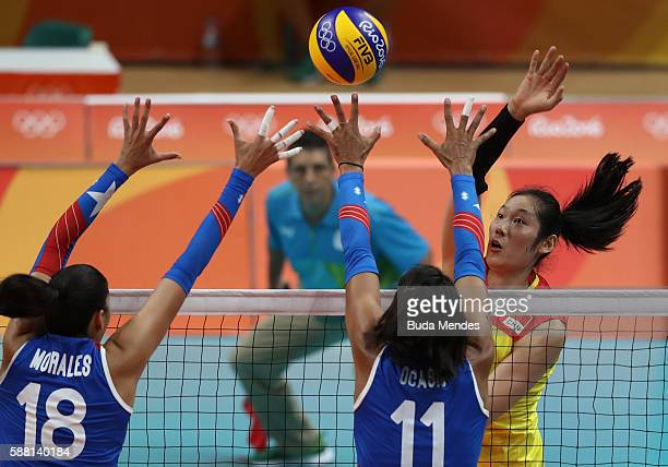 Ting Zhu of China spikes the ball against Lynda Morales and Karina Ocasio of Puerto Rico during the women's qualifying volleyball match between the...