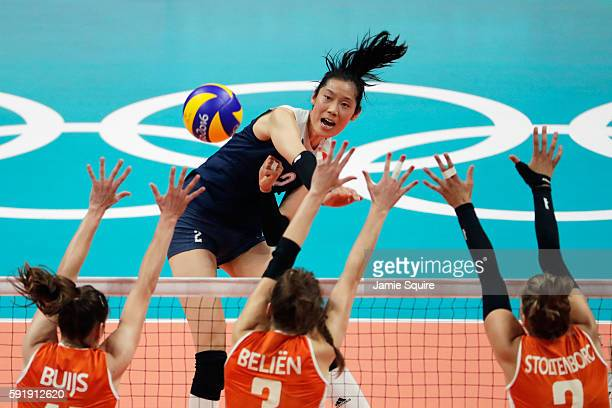 Ting Zhu of China strikes the ball at the Netherlands defence during the Women's Volleyball Semifinal match at the Maracanazinho on Day 13 of the...