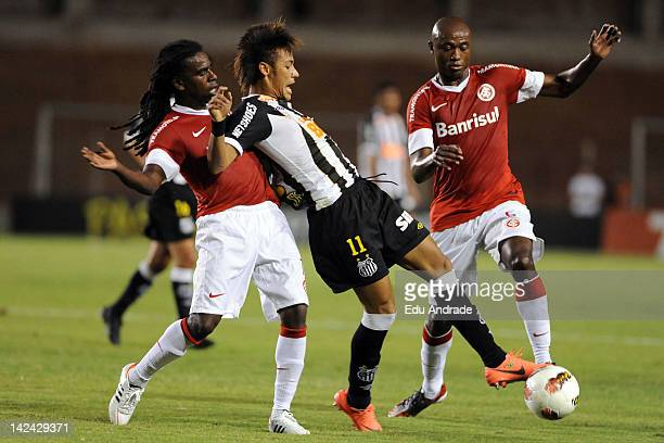 Tinga and Kléber from Internacional fight for the ball with Neymar of Santos during a match between Internacional and Santos at Beira Rio stadium as...