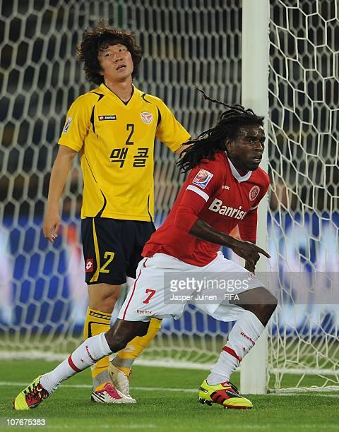 Tinga of Sport Club Internacional celebrates scoring his sides opening goal as Ko Jae Sung of Seongnam Ilhwa Chunma FC stands dejected during the...