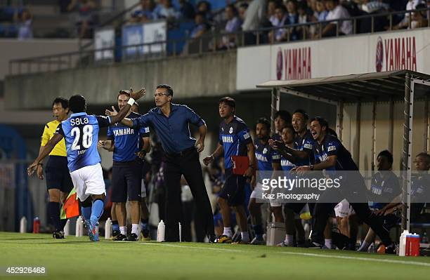Tinga whose real name is Paulo Cesar Fonseca do Nascimento celebrates scoring his team's first goal with head coach Pericles Chamusca during the J...