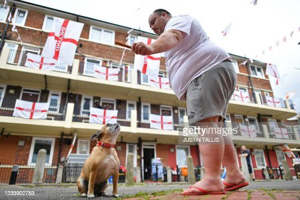 """""""Tinkerbell"""" the French bulldog performs for a treat as St George's flags, the national flag of England, are seen adorning residents' homes at the..."""