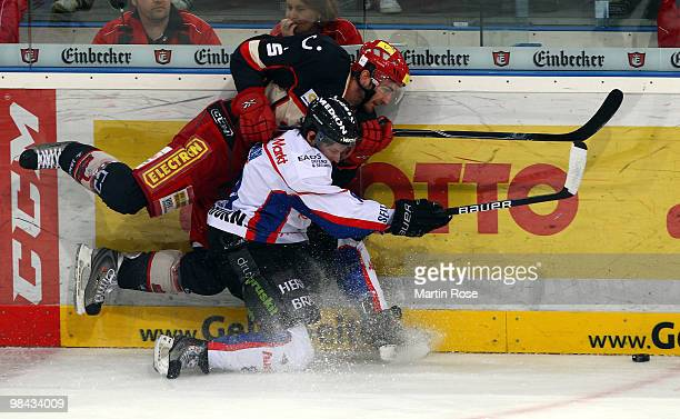 Tino Boos of Hannover and Dominik Walsh of Ingolstadt battle for the puck during the third DEL play off semi final match between Hannover Scorpions...