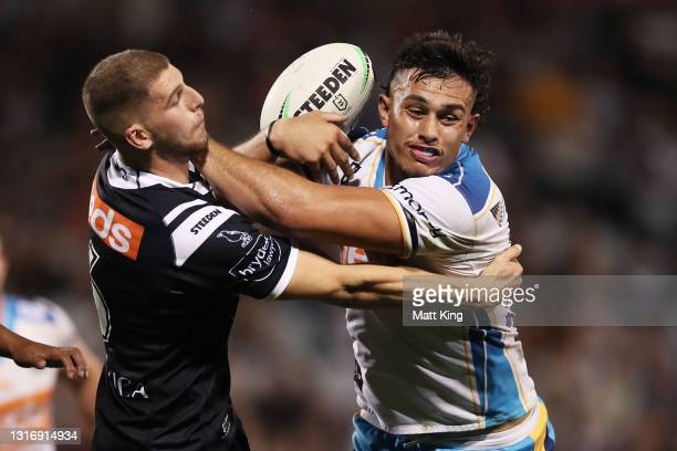 Tino Fa'asuamaleaui of the Titans is tackled by Adam Doueihi of the Tigers during the round nine NRL match between the Wests Tigers and the Gold...