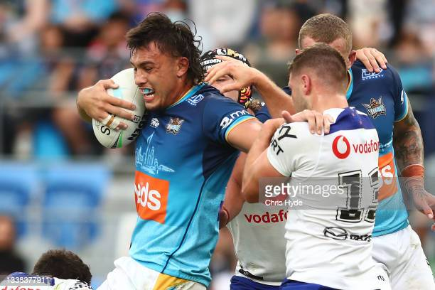 Tino Fa'asuamaleaui of the Titans is tackled during the round 25 NRL match between the Gold Coast Titans and the New Zealand Warriors at Cbus Super...