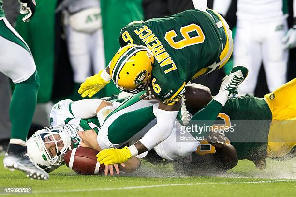 Tino Sunseri of the Saskatchewan Roughriders is sacked by Alonzo Lawrence and Almondo Sewell of the Edmonton Eskimos in the CFL Western SemiFinal...