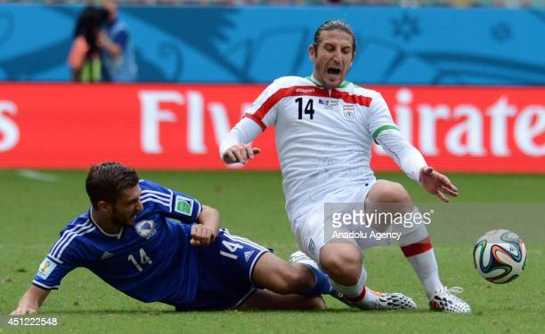 Tino Sven Susic of BosniaHerzegovina and Andranik Timotian of Iran vie for the ball during the 2014 FIFA World Cup Group F soccer match between...