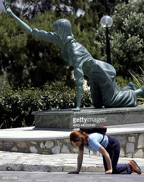 File picture of a Greek Orthodox woman on the Cycladic island of Tinos taken 17 July 2005 crawling past a statue representing the thousands of...