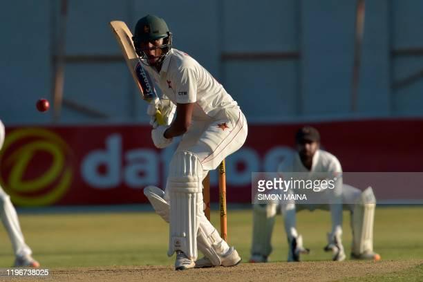 Tinotenda Mutombodzi plays a shot as Sri Lanka's Niroshan Dickwella looks on during the first day of the second Test cricket match between Zimbabwe...
