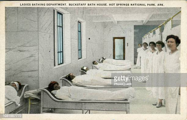 Tinted postcard from the Buckstaff Bath House shows female patrons wrapped in sheets as staff members stand by in the 'Ladies Bathing Department' Hot...