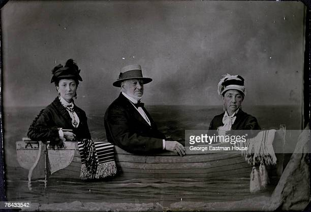 Tintype of two women and one man as they pose for a studio portrait 'in' a rowboat, mid 1870s. The man is possibly Samuel Castner Sr. (1798 - 1879] .