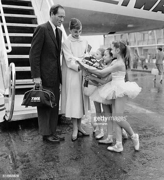 Tiny ballerinas from the Paris Opera give a big welcome and a bouquet to actress Audrey Hepburn as she arrives at the Paris airport with her husband,...