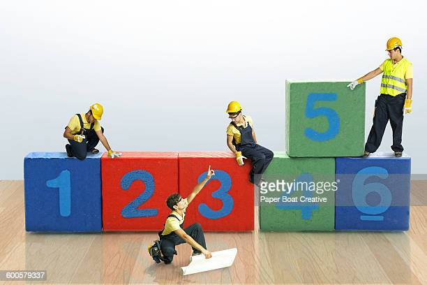 Tiny builders fixing toy blocks with numbers
