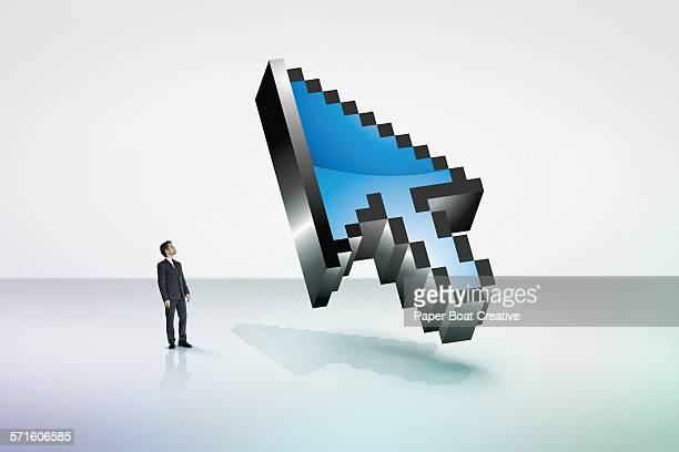 Tiny businessman looking at a giant 3D cursor