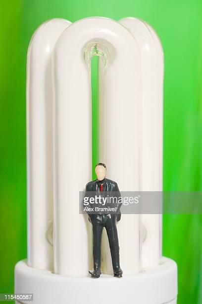 Tiny businessman standing on modern light bulb