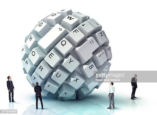 Tiny businessmen looking at a giant keyboard ball