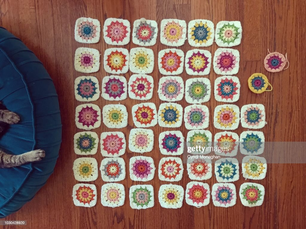 Tiny Colorful Granny Squares Crocheted and Spread Out on the Floor : Stock Photo