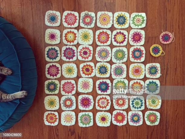 tiny colorful granny squares crocheted and spread out on the floor - crochet stock pictures, royalty-free photos & images
