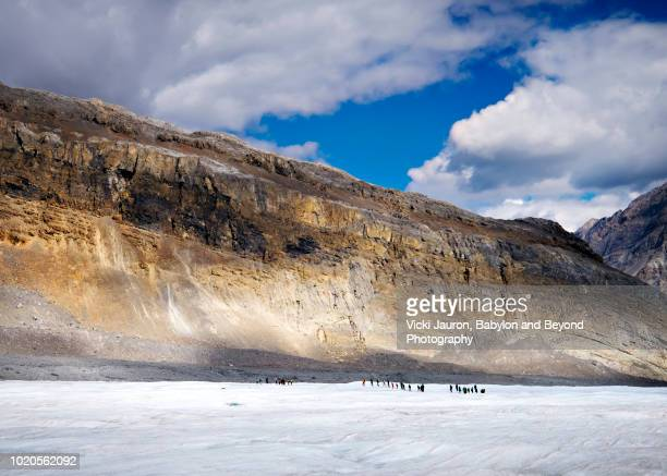 tiny figures on the ice at columbia icefields in alberta, canada - columbia icefield stock pictures, royalty-free photos & images