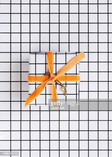Tiny golden key decorating a present on checked black and white paper with orange velvet ribbon