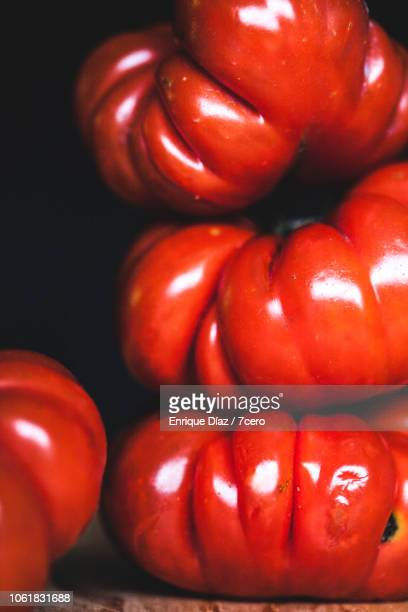 tiny heirloom tomatoes stacked on black - ugly wallpaper stock photos and pictures