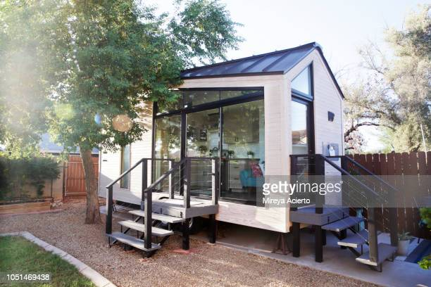 a tiny house with large glass windows, sits in the backyard, surrounded by a wooden fence and trees. - southwest usa stock pictures, royalty-free photos & images