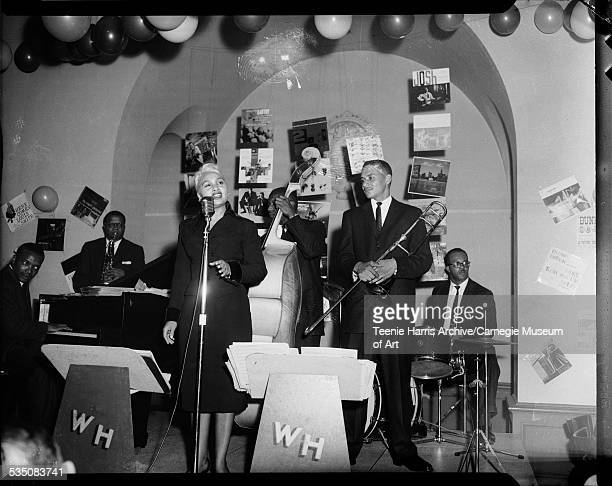Tiny Irvin performing at microphone in front of Walt Harper's band with Grover Mitchell on trombone Bert Logan Jr on drums Jimmy Royal on bass and...