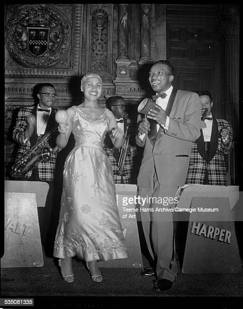 Tiny Irvin playing maracas and Walt Harper playing cowbell in front of band with Nate Harper with tenor saxophone Marion 'Boonie' Hazel with trumpet...
