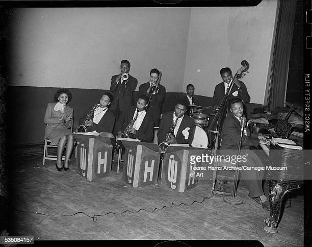 Tiny Irvin seated with eight musicians from Walt Harper's Band including saxophone players Bradley Bluett Earl Crandall and Nate Harper Billy Davis...