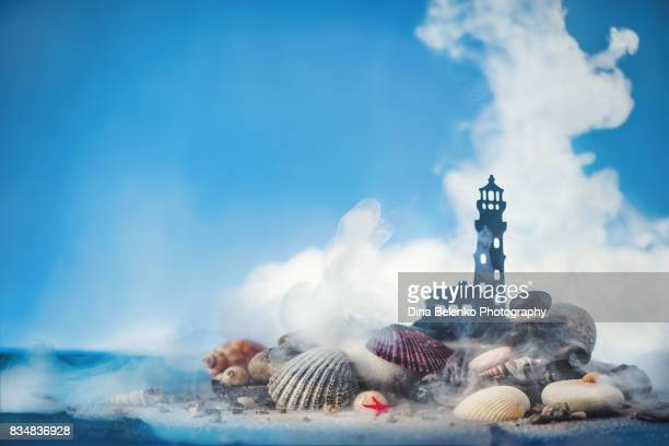 Tiny lighthouse silhouette with seashells, beach sand and smoke on a blue background.