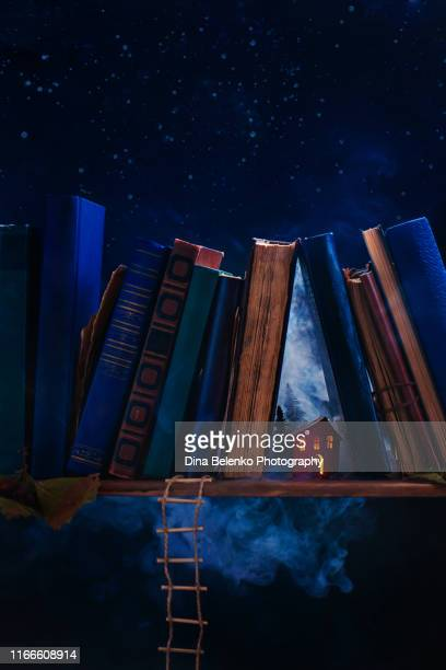 tiny paper house with light in windows on a book shelf. creative still life photography, tiny world metaphor. - literature stock pictures, royalty-free photos & images
