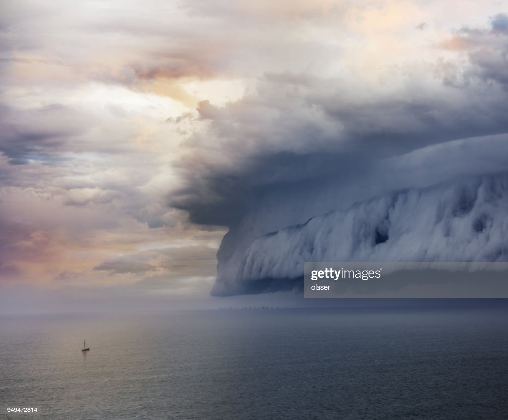 Tiny sailing boat and incoming storm : Stock Photo