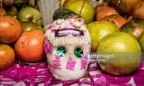A tiny skull made and decorated with sugar and fruit are placed as an offering at an altar in a cemetery during the commemoration of the Day of the...
