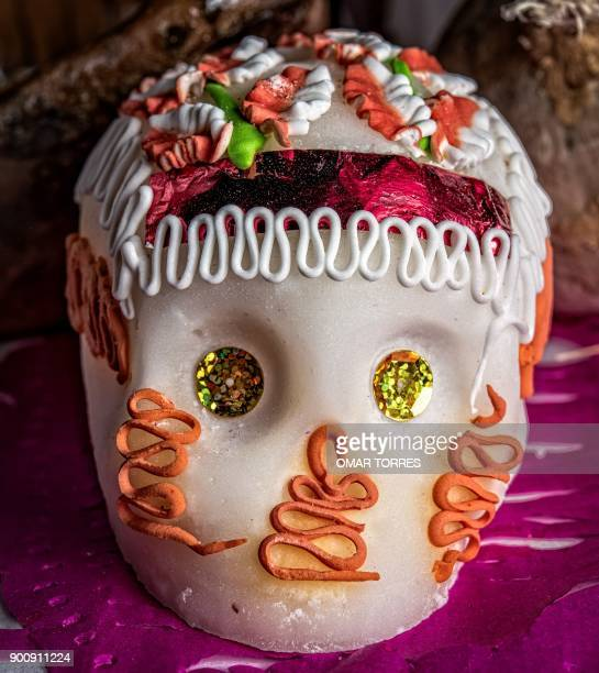 A tiny skull made and decorated with sugar is placed as an offering at an altar in a cemetery during the commemoration of the Day of the Dead in...