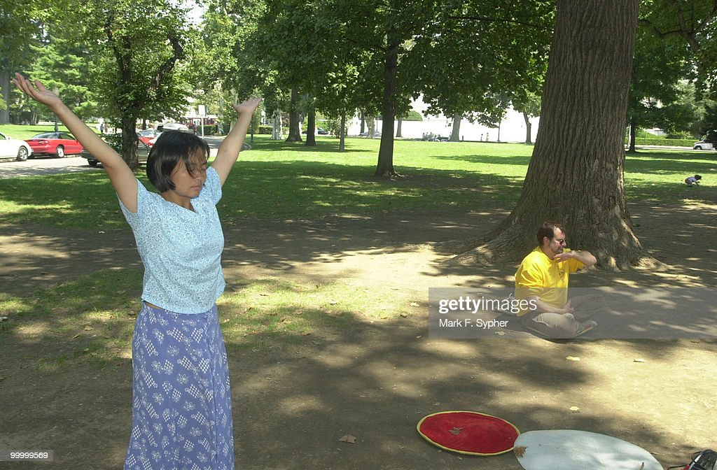 Tiny Tang, of Fairfax, VA. and Robert Nappi, of Alexandria, VA. practice Falun Dafa on a sweltering Tuesday afternoon on the east lawn of the Capital.