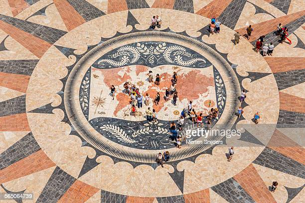 Tiny tourists on court with worldmap mosaics