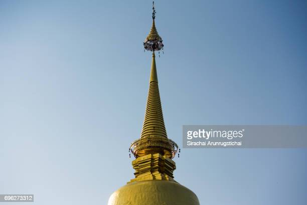 Tip of a golden pagoda against the blue sky