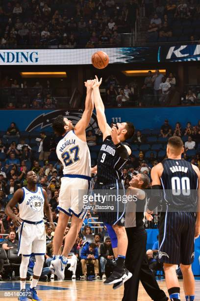Tip off between Zaza Pachulia of the Golden State Warriors and Nikola Vucevic of the Orlando Magic on December 1 2017 at Amway Center in Orlando...