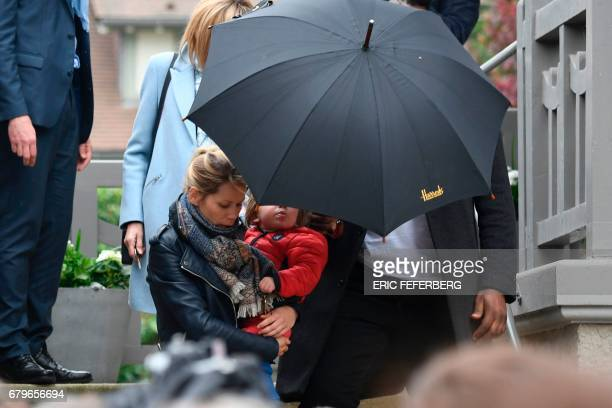 Tiphaine Auziere stepdaughter of French presidential election candidate for the En Marche movement Emmanuel Macron carries her child as people gather...
