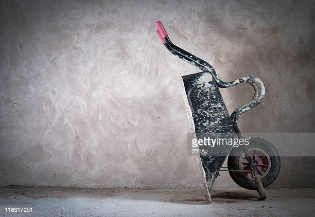 Tipped over wheelbarrow against beige background