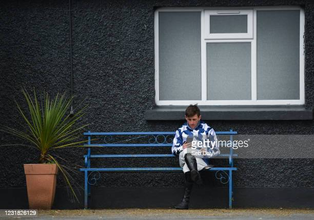 Tipperary , Ireland - 20 March 2021; Jockey Barry John Foley relaxes as he talks on his mobile phone prior to racing at Thurles Racecourse in...